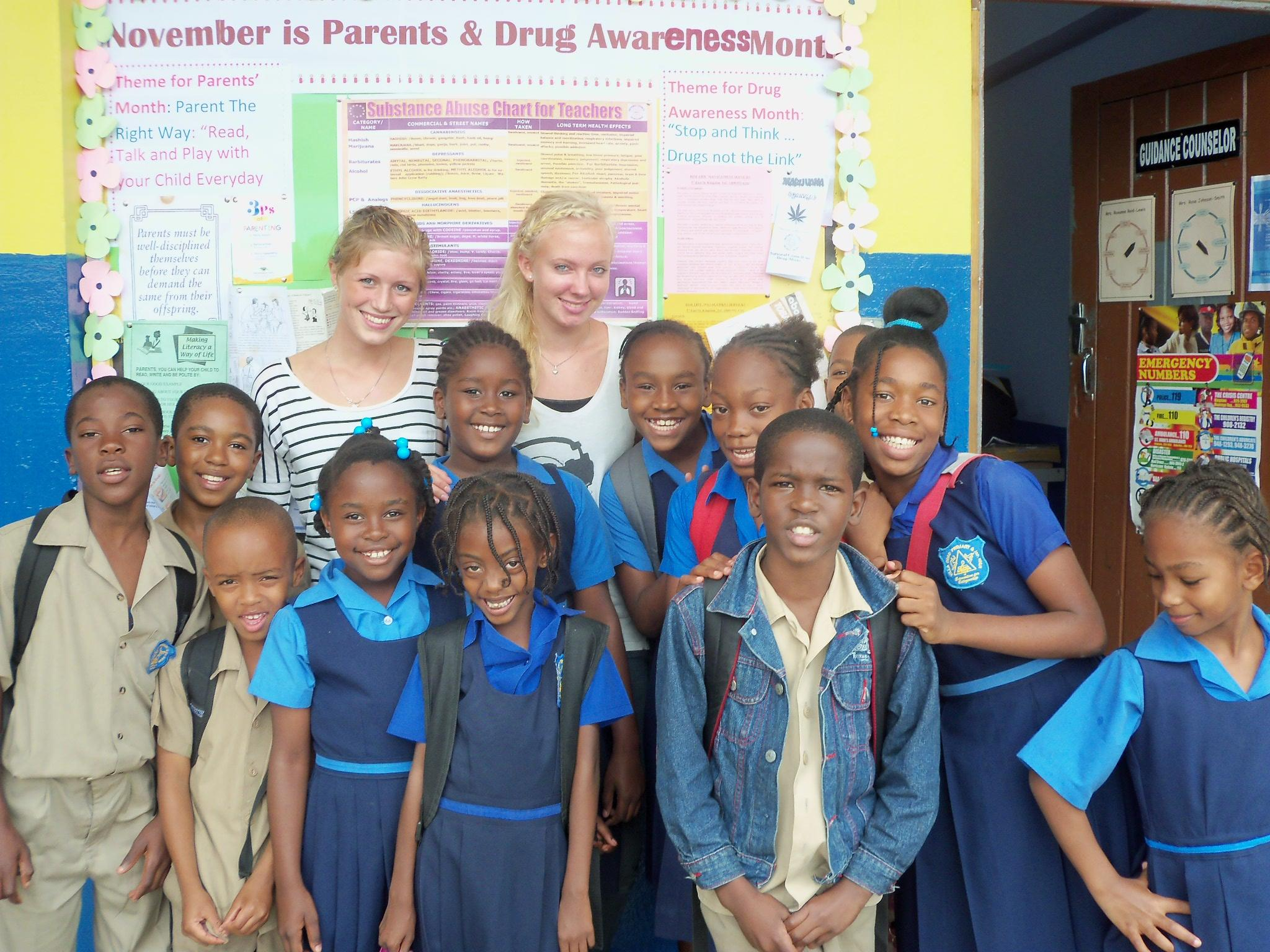 Projects Abroad volunteers teaching in Jamaica pose with their students